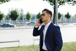 uomo in giacca e cravatta parlando al telefono foto