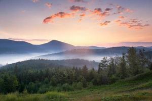 splendido paesaggio montano all'alba con bella nebbia e nuvole