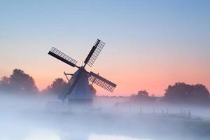 affascinante mulino a vento olandese nella nebbia mattutina