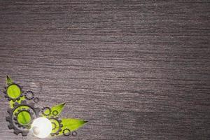 foglie e ruote dentate su fondo in legno foto