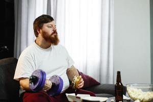 uomo grasso che si esercita mentre si siede con il cibo davanti a un televisore