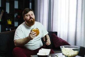 uomo grasso mangia hamburger con birra seduto al tavolo davanti alla tv