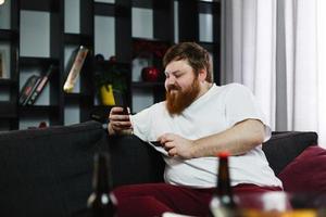 uomo grasso digita il numero di una carta di credito nel suo telefono seduto sul divano