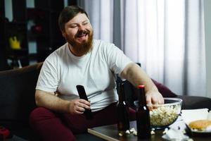 felice uomo grasso si siede sul divano e guarda la tv con popcorn e birra