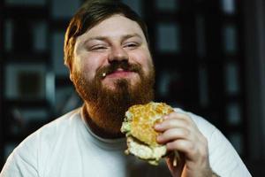 sorridente uomo grasso mangia hamburger