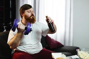 uomo che beve una birra e sollevamento pesi
