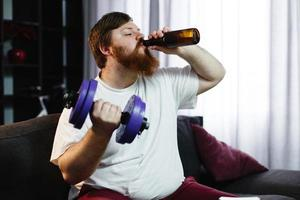 uomo che beve una birra mentre solleva pesi