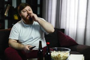 felice uomo grasso mangia pop-corn foto