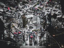 tokyo, giappone, 2018: i turisti escono dalla scala mobile con mirroring nella strada trafficata