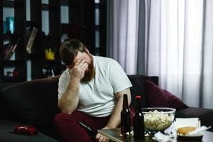 uomo grasso triste si siede sul divano