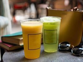 cocktail di frutta sul tavolo con occhiali da sole e libri