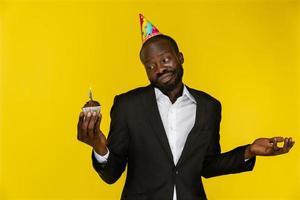 bell'uomo d'affari sembra perso mentre tiene una torta di compleanno
