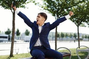 ragazzo felice seduto su una panchina nel parco