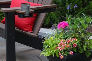 pianta floreale rosa e rossa accanto alla sedia adirondack in legno marrone