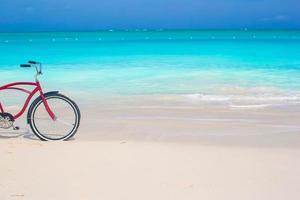 bici su una spiaggia tropicale contro l'oceano turchese e il cielo blu
