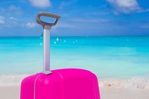 valigia rosa su una spiaggia