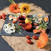 pesce fresco e disposizione di frutti di mare su sfondo di pietra nera foto