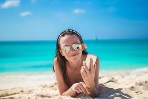 donna sdraiata su una spiaggia con il suo telefono