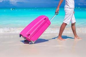 da vicino un uomo tira i bagagli sulla sabbia bianca