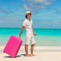uomo con bagagli su una spiaggia