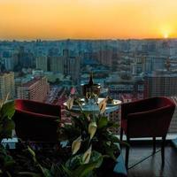 bottiglia di champagne e bicchieri al ristorante con vista sulla città al tramonto