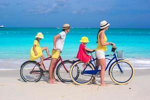 giovani genitori e bambini che vanno in bicicletta su una spiaggia