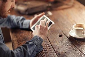 giovane uomo utilizzando un tablet touch screen foto