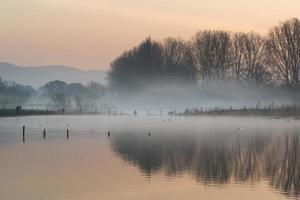 paesaggio del lago nella nebbia con il bagliore del sole all'alba foto