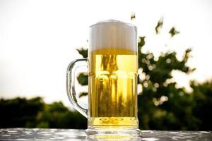 una pinta di birra su sfondo naturale linea degli alberi foto