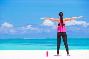 donna che fa yoga su una spiaggia
