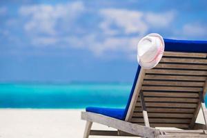 primo piano di una sedia a sdraio e cappello bianco su una spiaggia