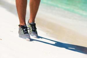 primo piano delle scarpe di un corridore su una spiaggia