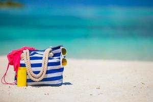 borsa blu a righe con accessori da spiaggia su una spiaggia