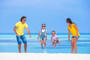 famiglia saltare la corda su una spiaggia