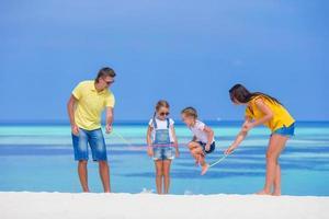 famiglia divertirsi con una corda per saltare in una spiaggia