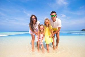 famiglia in acqua su una spiaggia tropicale