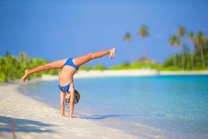 ragazza che fa una verticale in spiaggia