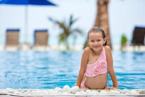 ragazza divertirsi in una piscina all'aperto foto
