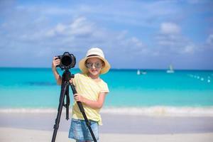 ragazza con la macchina fotografica su un treppiede su una spiaggia