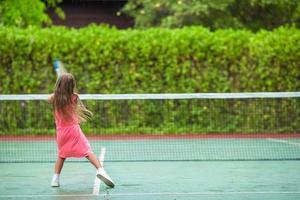 ragazza che gioca a tennis in un tribunale foto