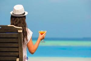 donna con bicchiere da cocktail vicino alla piscina