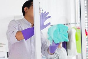 uomo asiatico che pulisce una finestra