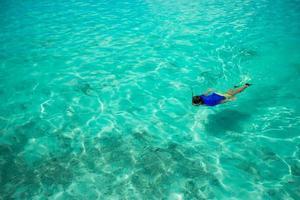 uomo lo snorkeling in limpide acque tropicali