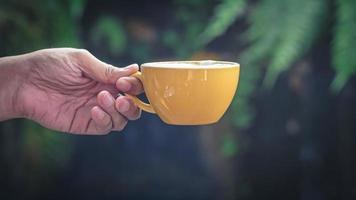 primo piano della mano isolata che tiene tazza gialla