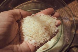 la mano tiene i chicchi di riso