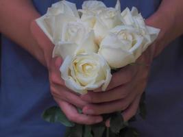 persona in possesso di un bouquet di rose bianche