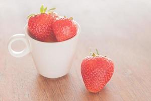 tre fragole e una tazza foto
