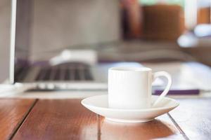 mini tazza di caffè bianco sulla postazione di lavoro foto