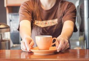 barista che offre una tazza di caffè arancione foto