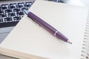 primo piano di un taccuino e di una penna su un computer portatile
